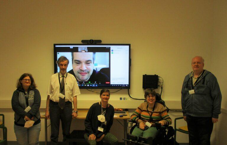 Gruppenbild: Workshopteilnehmer und Teilnehmerinnen mit Peer-Streitschlichter und Trainerin. Ein Workshopteilnehmer ist am Bildschirm an der Wand zugeschalten.